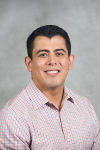 Image of Dr. Jorge Ramallo - A man with a light pink plaid shirt, tan skin, and black hair smiling. Gray background.