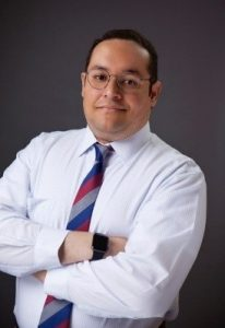 Image of Dr. Michael Potnek - a man in a white shirt with a red, gray, and blue tie, and his arms crossed. He has tan skin, black hair, and circular glasses. Dark gray background.