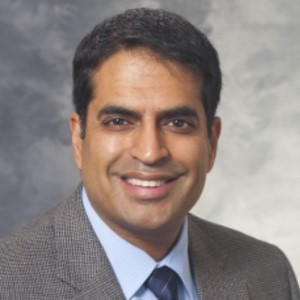 Image of Dr. Ajay Sethi - a man smiling, wearing a gray plaid suit jacket, a light blue collared shirt, and a dark blue tie. He has tan skin and black hair. Cloudy gray background.