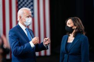 Masked Biden with perpendicular arms and fists clenched, masked Harris stands to the right. An American flag in the background