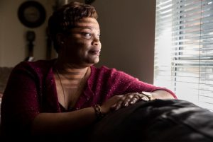 Black woman sitting on couch in a dark room looks out bright window with blinds.