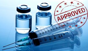"Two vials and two syringes on a reflective surface. Circular, red ""APPROVED"" stamp with stars in top right corner."