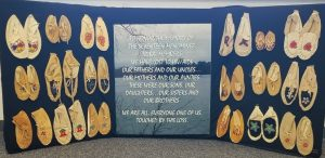 Poster with moccasins of various design and size with a quote of below caption as a quote in center