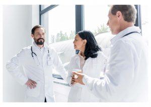 Stock photo of 3 doctors (2 male, 1 female) talking by a window.